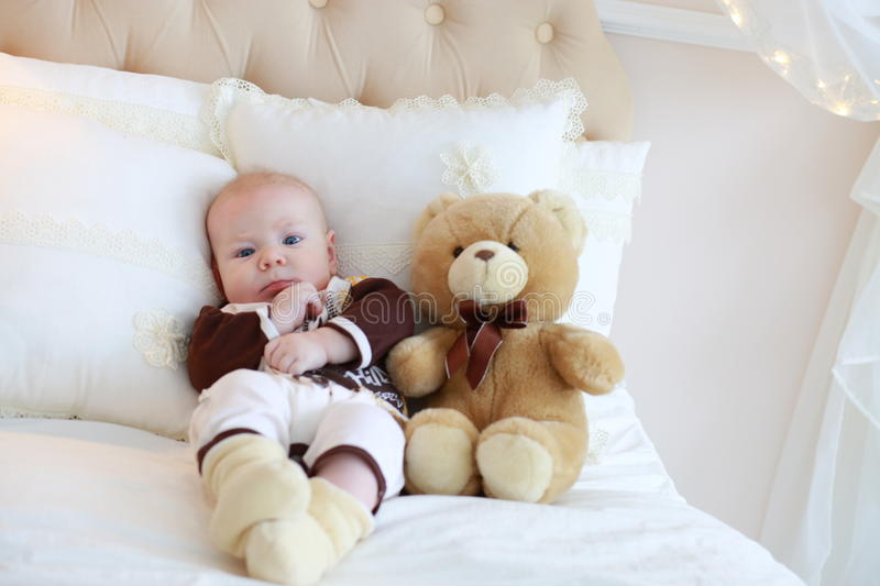 Portrait of a cute baby lying on the white bed. With teddy bear stock photography