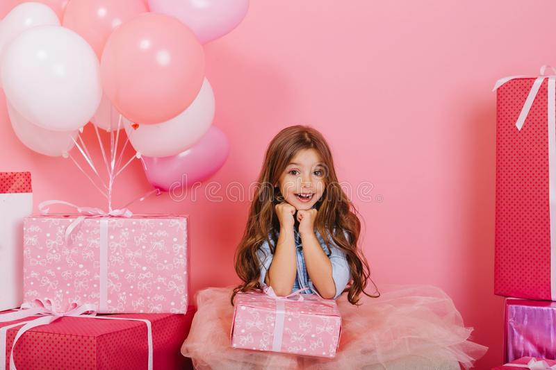 Portrait cute birthday kid expressing to camera suround big giftboxes, balloons  on pink background. Amazing royalty free stock photo