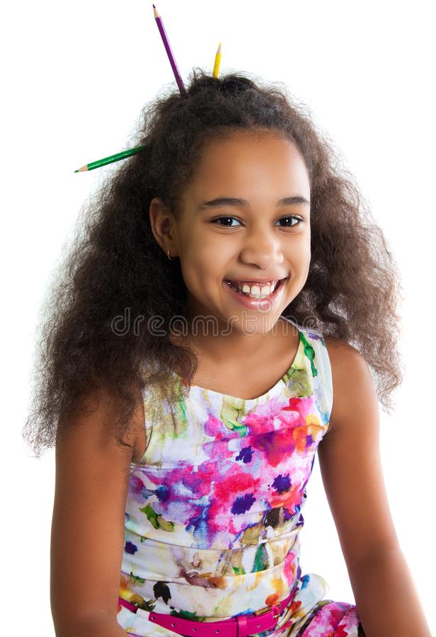 Portrait of a cute black girl on a white background. Positive human emotions. The child smiles. Multi-colored pencils sticking out royalty free stock image