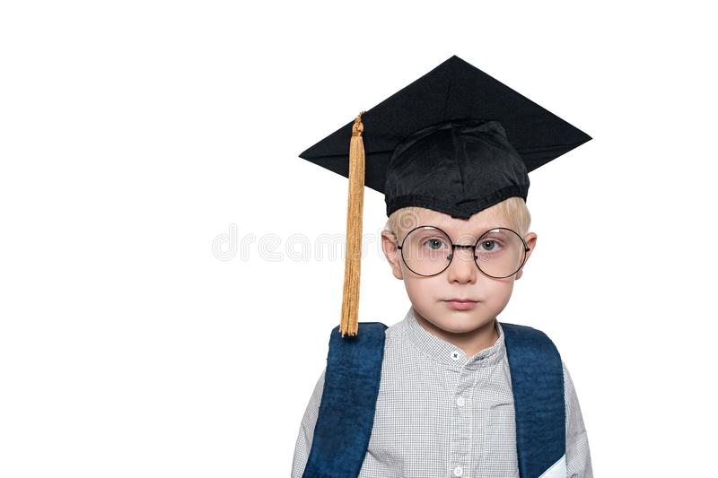 Portrait of a cute blond boy in big glasses, academic hat and a school bag. White background. Place for text royalty free stock photo