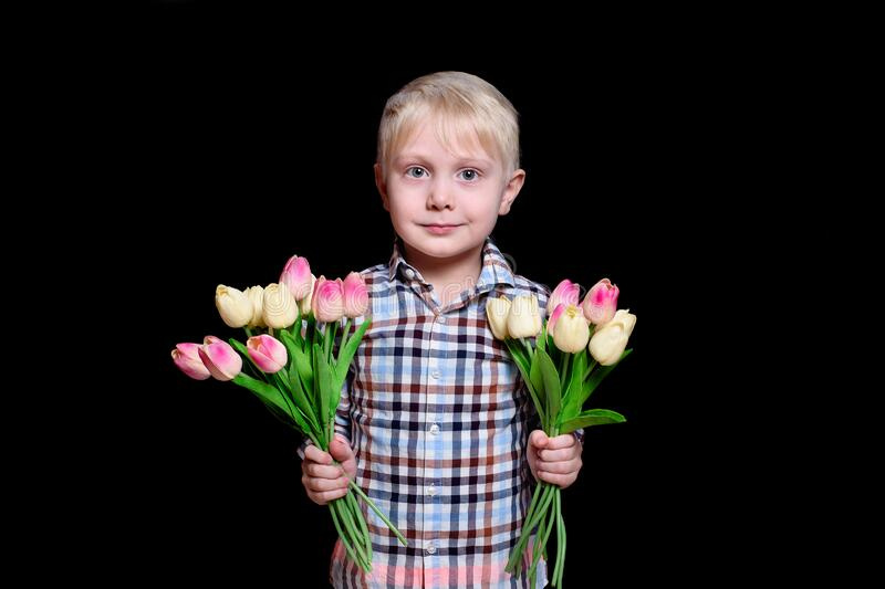 Portrait cute blond boy with a two bouquets of tulips. Black background stock photos