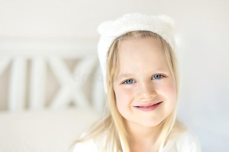 Portrait cute blond girl. Smilling kid in white hat. Child on bed in bright room. Adorable baby wearing funny hat wit stock image
