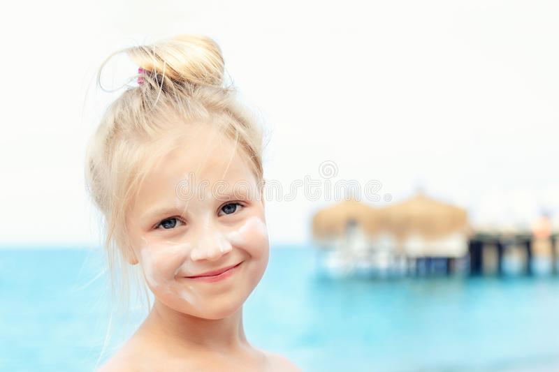 Portrait of cute blond kid girl applying sunscreen protection creme on  face. Mom using sunblocking lotion to protect baby. During summer sea vacation royalty free stock images