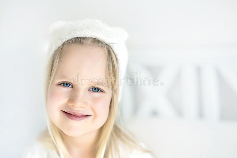 Portrait cute blond preschooler girl. Smilling kid in white hat. Child on bed in nursery room. Adorable baby wearing funny hat royalty free stock images