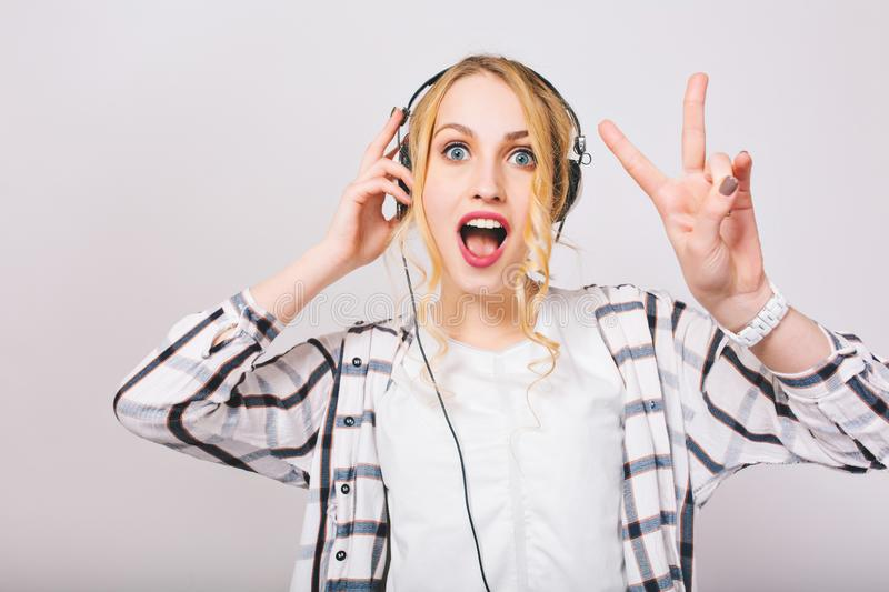 Portrait of cute blonde curly girl in headphones listening music with surprised face and dancing. Charming blue-eyed stock images