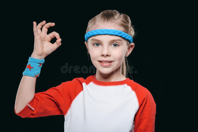 Portrait of cute blonde girl in sportswear showing ok sign and smiling at camera royalty free stock images