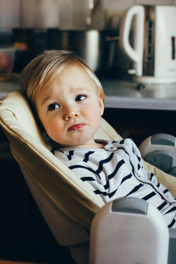 Portrait of a cute blonde toddler. Beautiful baby boy sitting in a high chair waiting, looking away. He is sad stock photo