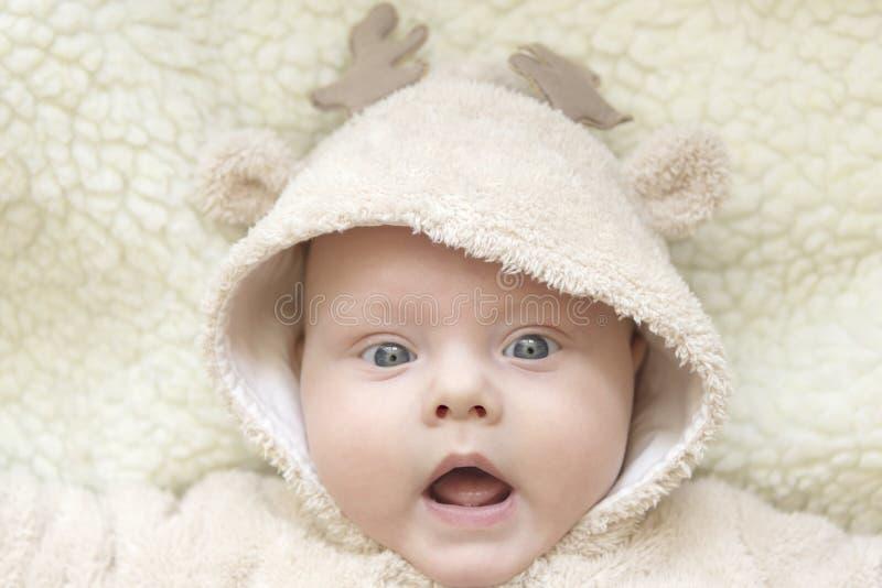 Portrait of a cute kid in a deer suit. Portrait of a cute blue-eyed kid in a deer suit stock photo