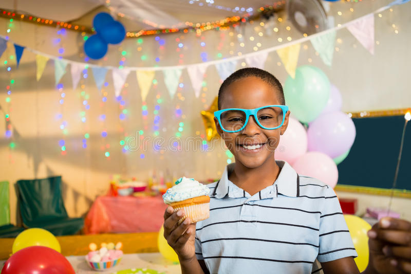 Portrait of cute boy holding cupcake during birthday party. At home stock photo