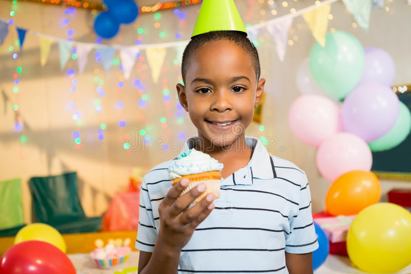 Portrait of cute boy holding cupcake during birthday party. At home stock photography