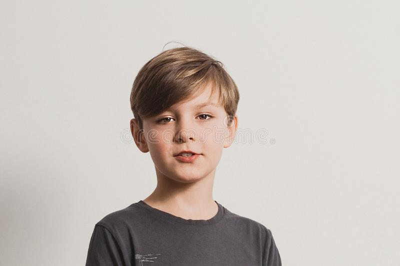 A portrait of cute boy saying something. Looking at camera, dark grey shirt, white wall. Copy space for your text and design stock photos