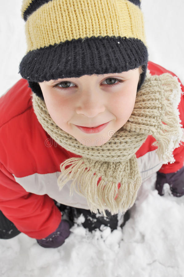 Portrait of a cute boy in the snow royalty free stock images