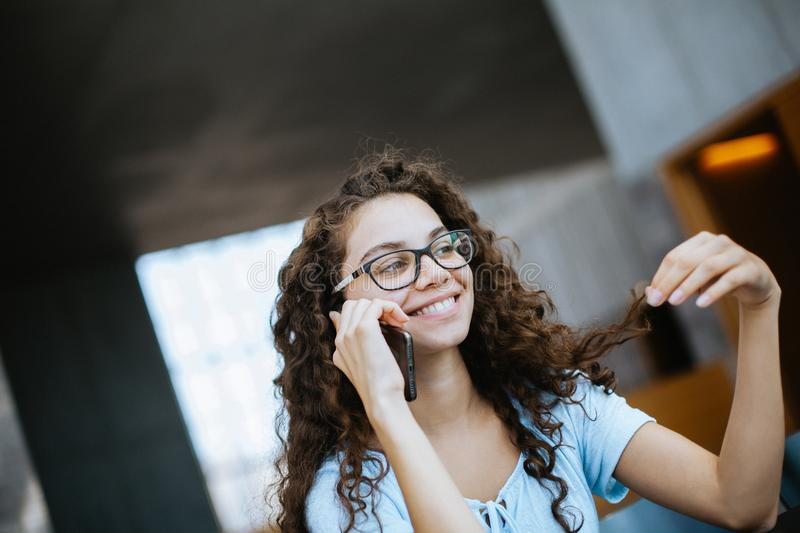 Cute brazilian girl with curly hair has a funny and exciting conversation on the phone stock image