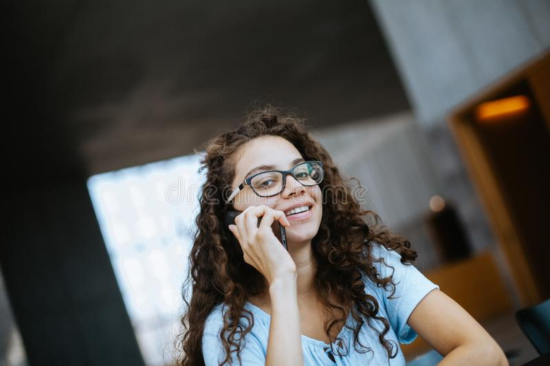 Cute brazilian girl with curly hair has a funny and exciting conversation on the phone stock images