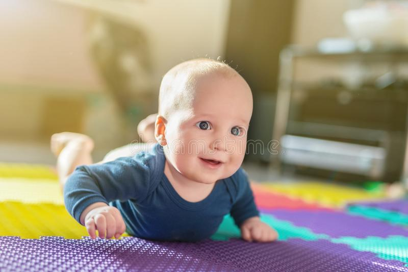 Portrait of cute caucasian baby boy crawling on soft playing mat indoors. Adorable child having fun making making first steps on f royalty free stock photos