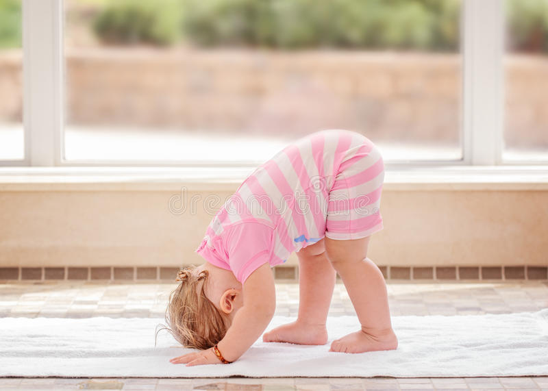 Portrait of cute Caucasian baby girl doing physical fitness exercises yoga on floor stock photos