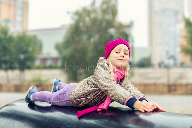 Portrait of cute caucasian blond little girl having fun playing at modern outdoor playground at city park in autumn. Adorable young happy child enjoying and royalty free stock photos