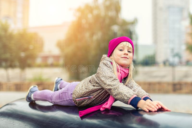 Portrait of cute caucasian blond little girl having fun playing at modern outdoor playground at city park in autumn. Adorable. Young happy child enjoying and stock photography