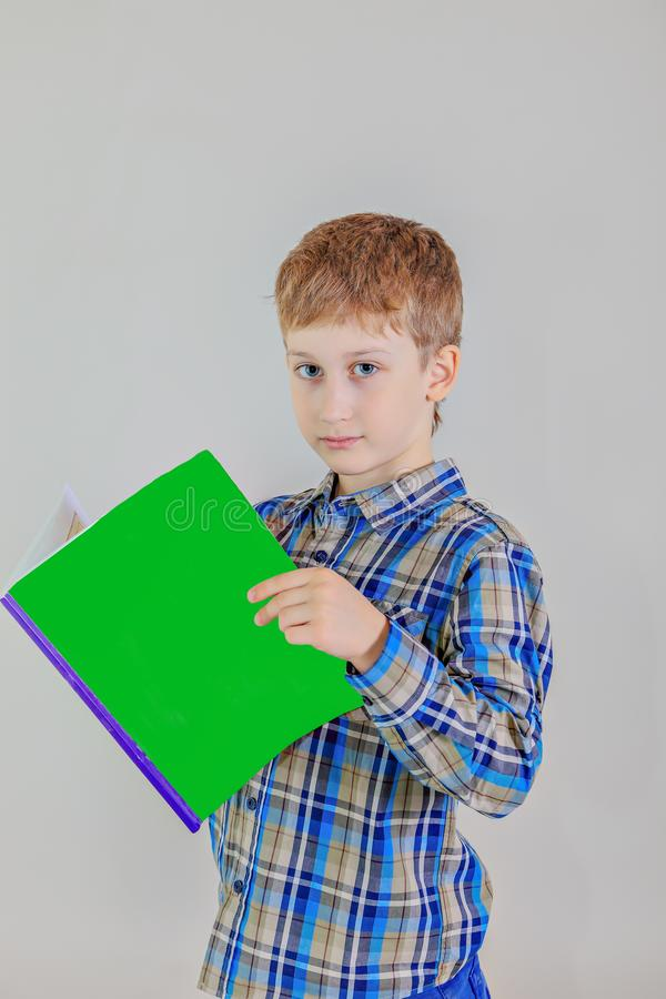 Portrait of cute redhead сaucasian boy,elementary school student with book on grey background royalty free stock photography
