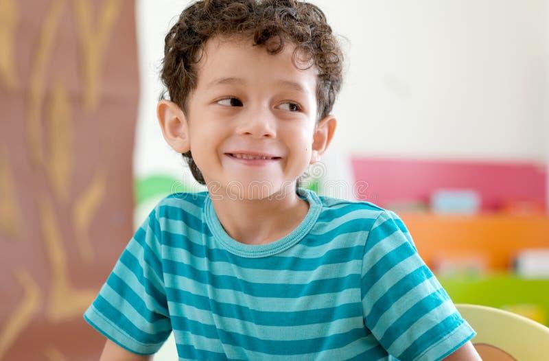 Portrait of cute caucasian boy smiling in classroom school, Happy white american boy kid in kindergarten, elementary classroom, stock photography