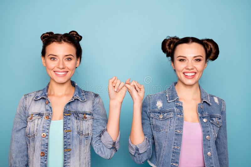 Portrait of cute charming satisfied hipsters person isolated holding hands together placing pinkies showing peace stock photos