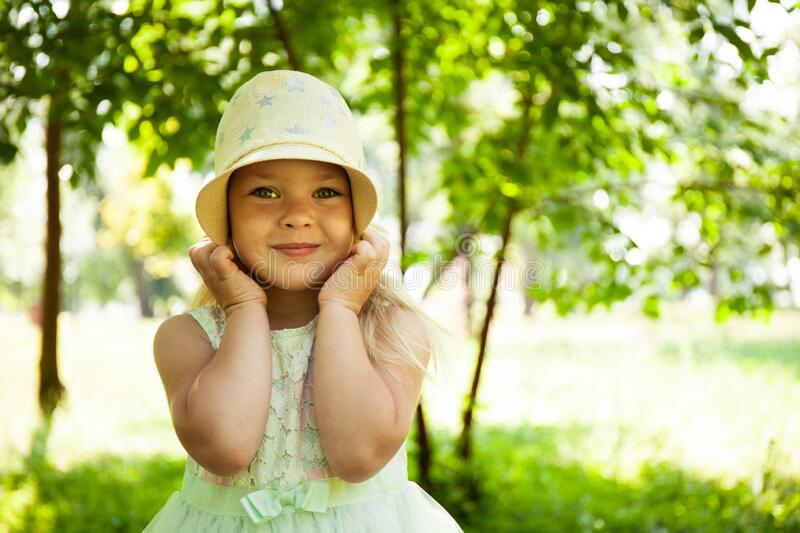 Portrait of cute child girl model in hat smiling in park or outdoor. Happy childhood, summer holidays and vacations royalty free stock photography