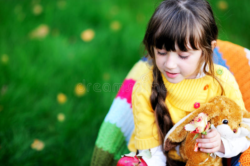 Portrait of cute child girl sitting outdoors stock photography
