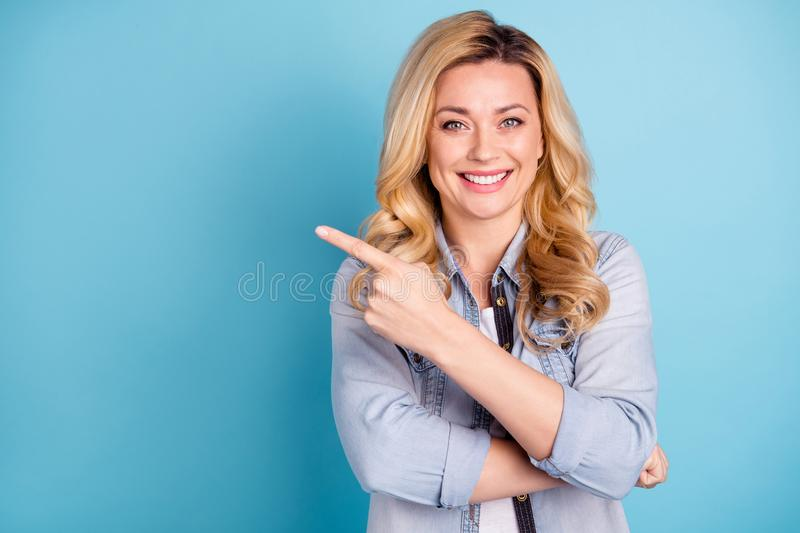 Portrait of cute confident person pointing at copy space showing adverts isolated over blue background royalty free stock photos