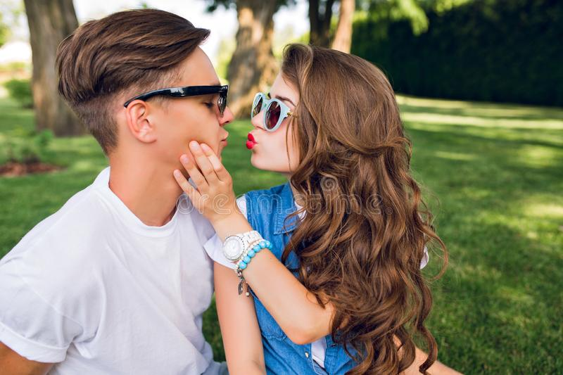 Portrait of cute couple of young people on grass in park. Pretty girl with long curly hair shows a kiss to handsome guy stock photos