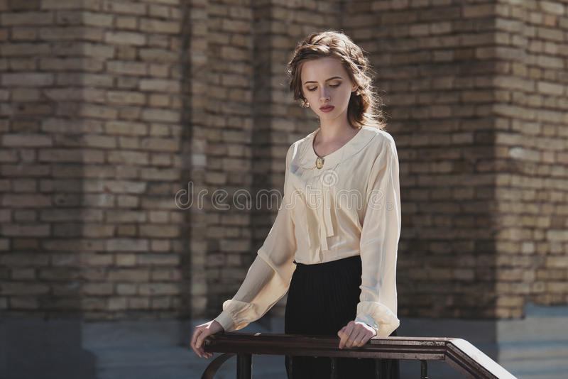 Portrait of a cute dreamy girl wearing retro blouse and skirt outdoors. Soft vintage toning. royalty free stock photography