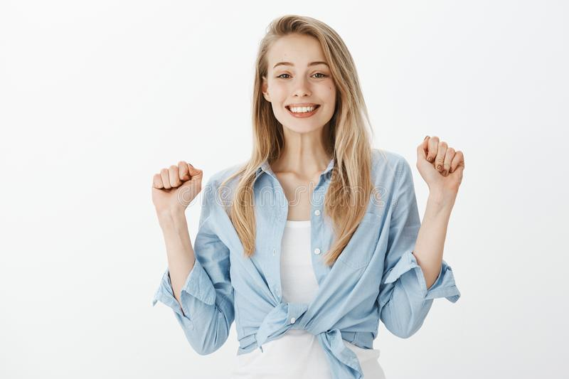 Portrait of cute excited european female student with blond hair, raising clenched fists and smiling cheerfully, feeling stock photo