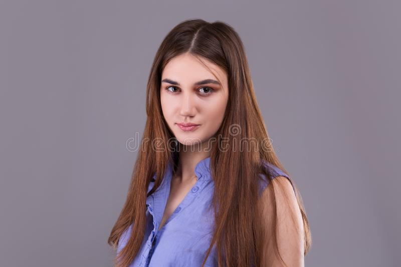 Portrait of cute fashionable young brunette woman in blue shirt. royalty free stock photos