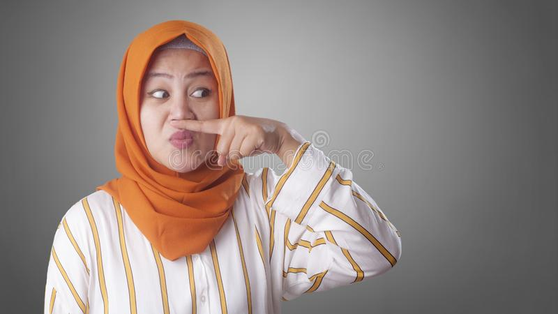 Cute Asian Muslim Lady Close Her Nose. Portrait of cute funny Asian muslim lady wearing hijab close her nose because of bad disgusting smell odor indonesian stock photography