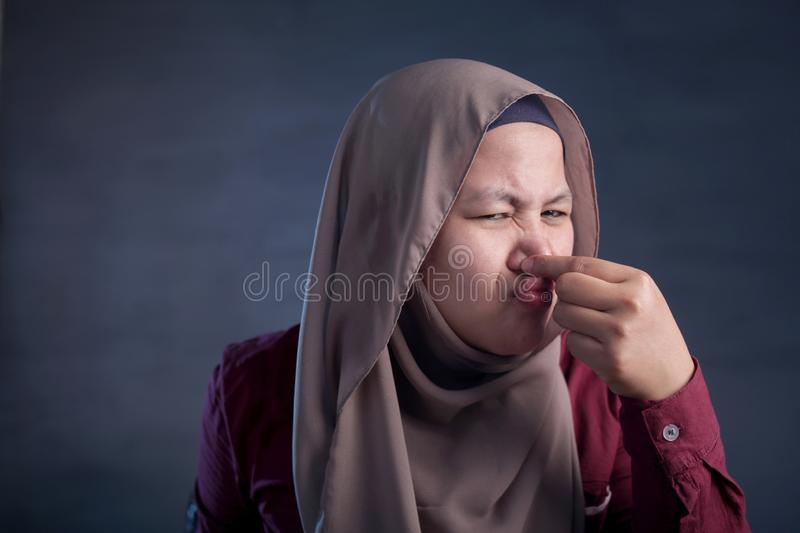 Cute Asian Muslim Lady Close Her Nose. Portrait of cute funny Asian muslim lady wearing hijab close her nose because of bad disgusting smell odor, indonesian stock photos