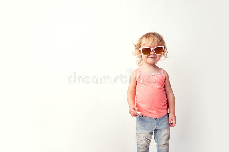 Portrait of a cute funny Caucasian baby hipster girl in a t-shirt jeans and sunglasses with a tablet from motion sickness in her royalty free stock image