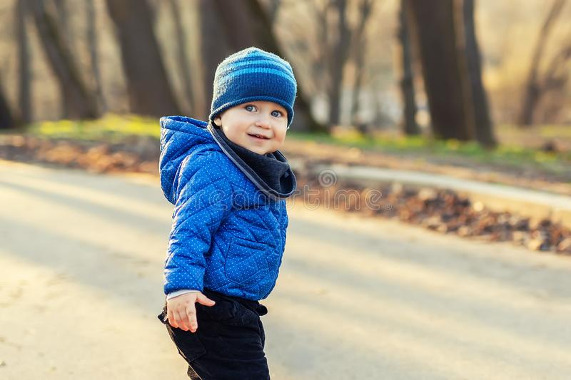 Portrait of cute funny caucasian toddler boy in blue jacket and hat enjoying walking at autumn park or forest during sunset with stock images