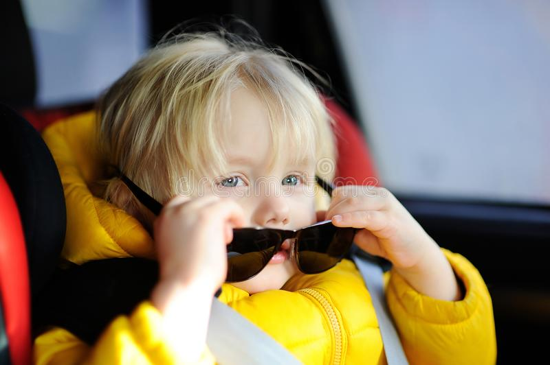 Portrait of cute funny little boy wearing father`s sunglasses sitting in car seat royalty free stock images