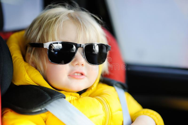 Portrait of cute funny little boy wearing father`s sunglasses sitting in car seat stock photo
