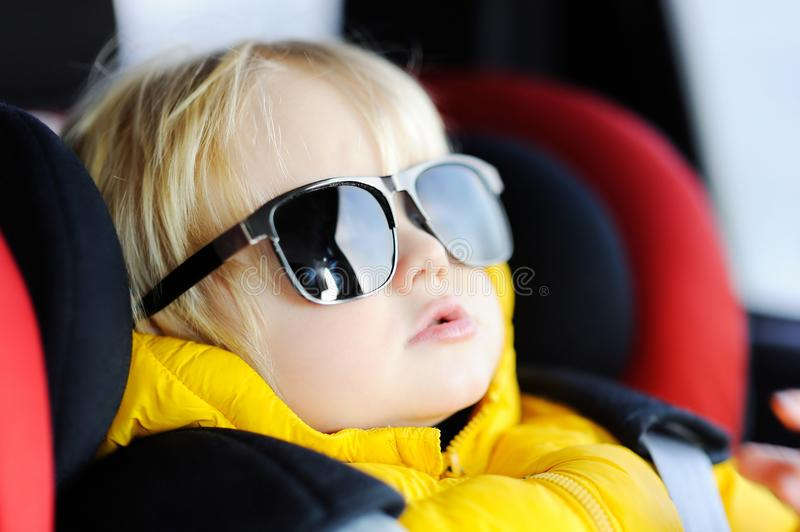 Portrait of cute funny little boy wearing father`s sunglasses sitting in car seat royalty free stock image