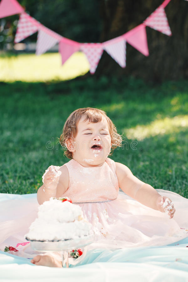 Portrait of cute funny upset sad crying Caucasian baby girl in pink tutu dress celebrating her first birthday stock image