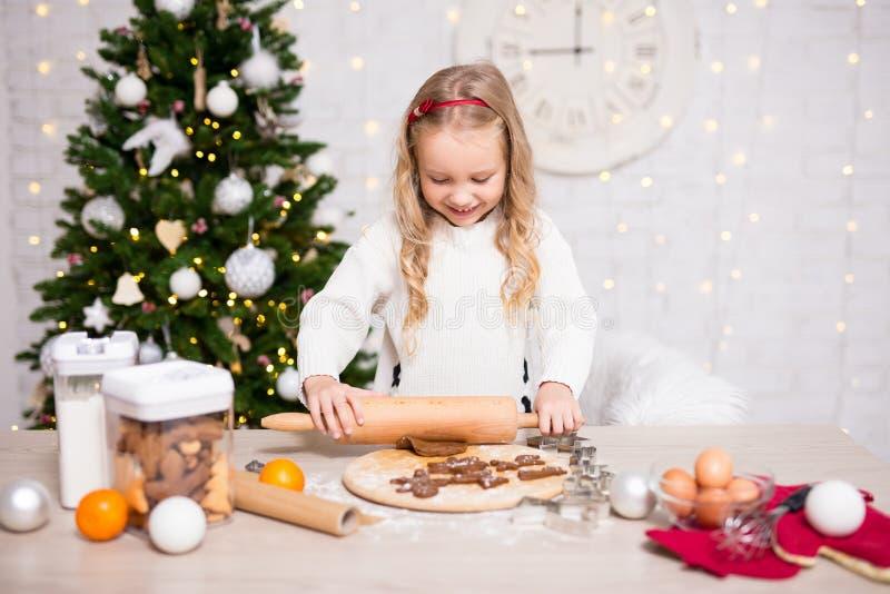Portrait of cute girl baking Christmas cookies in kitchen with C. Portrait of cute little girl baking Christmas cookies in kitchen with Christmas tree stock photos