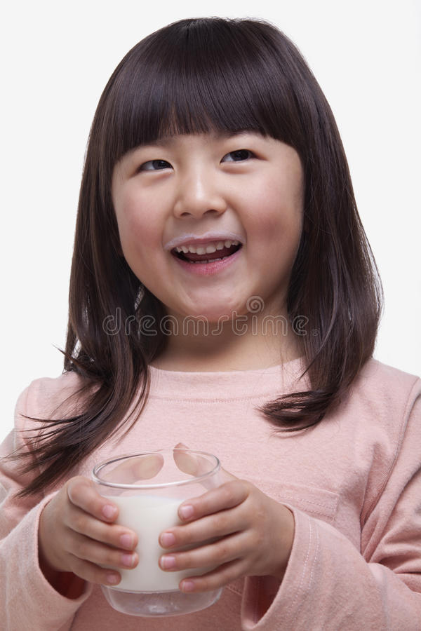 Portrait of cute girl with bangs drinking a glass of milk with a milk moustache stock photos