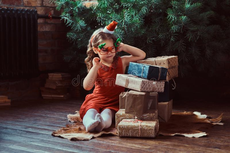 Portrait of a cute girl with blonde curly hair wearing a red dress and little Santa`s hat sitting on a floor surrounded stock photography
