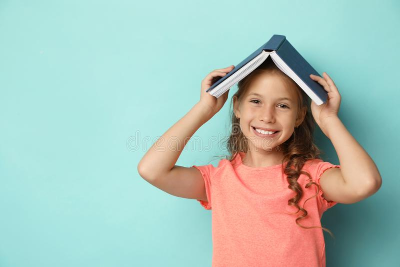 Portrait of cute girl with book on turquoise background. Reading concept stock image