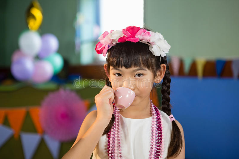 Portrait of cute girl drinking tea during birthday party royalty free stock photography