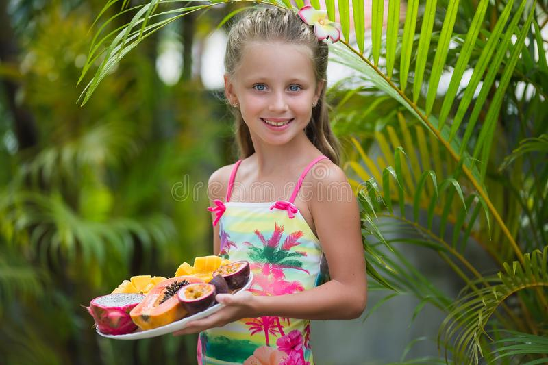 Portrait of a cute girl with exotic fruits on a background of palm trees stock image