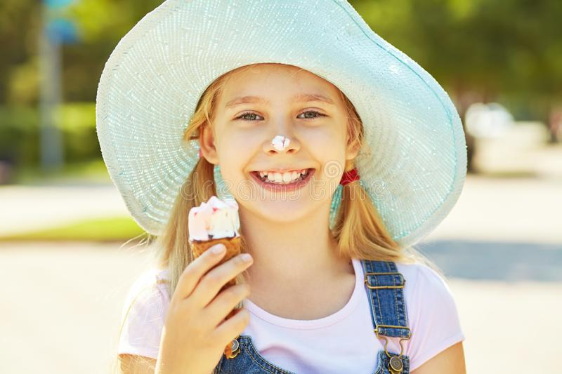 Portrait of a cute girl in hat with ice cream in park. child outdoors royalty free stock image