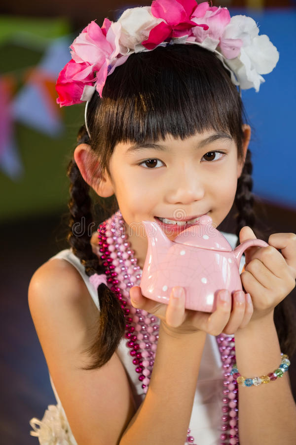 Portrait of cute girl holding toy teapot during birthday party stock image