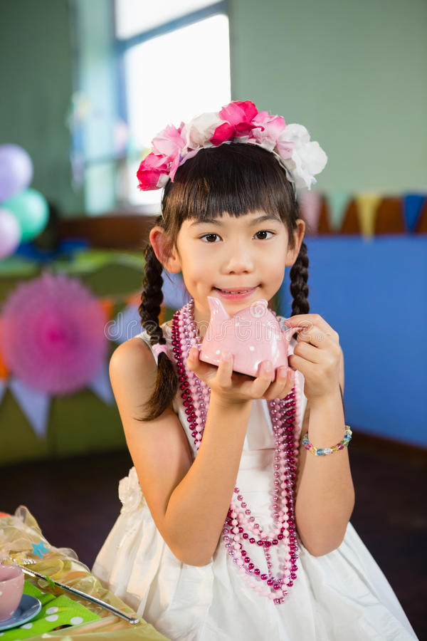 Portrait of cute girl holding toy teapot during birthday party stock photos