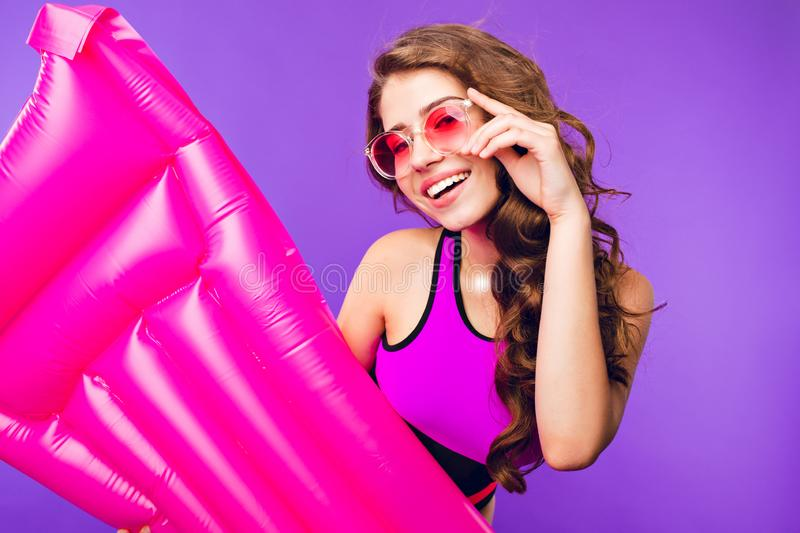 Portrait of cute girl with long curly hair on purple background. She wears swimsuit, holds pink air mattress in hand and stock photos